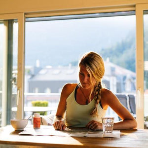 sportive blonde girl doing breakfast with crownhealth force vegan sports nutrition while studying a map