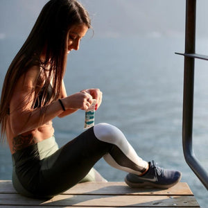 sporty girl eating crown health organic protein bars on lake zurich