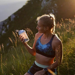 woman drinking from a sports protein shaker on the mountain with woods surrounding her