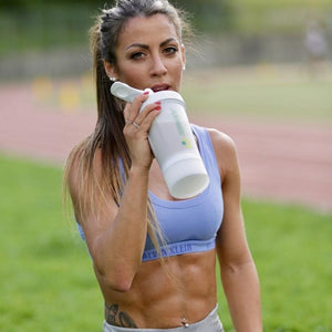 fit sexy woman six pack abs drinking vegan protein recovery shake Crownhealth after running intervals training