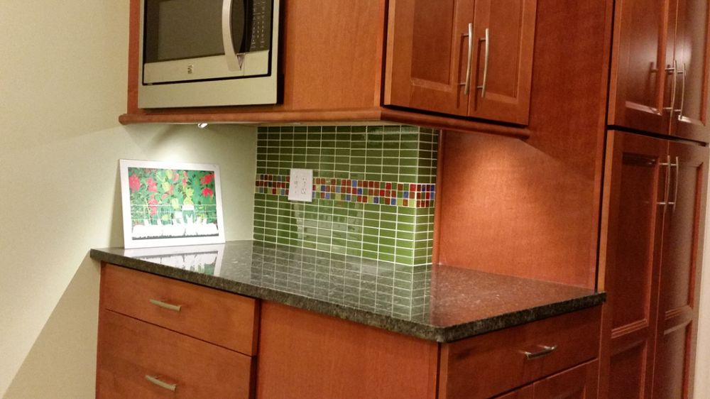 Beautiful green kitchen with a splash of multi-colored tile