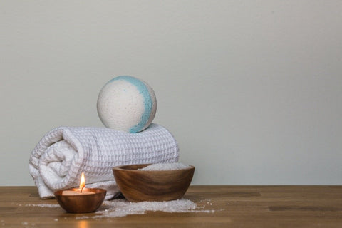towel and bathrobe with a bath bomb and candle