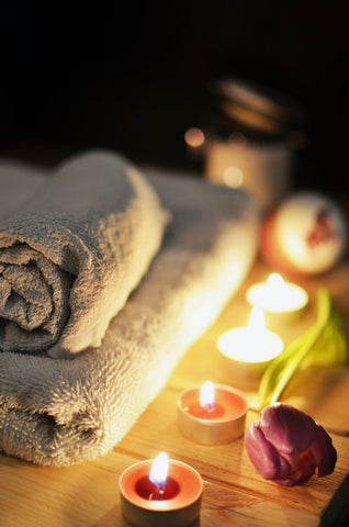 Towels and candles arranged for a relaxing sauna session.
