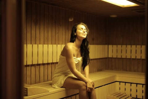 A woman enjoying a relaxing sauna session for weight loss