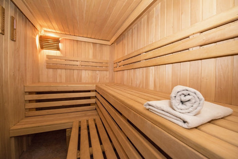 A sauna from the inside, looking clean and relaxing with towels lying around