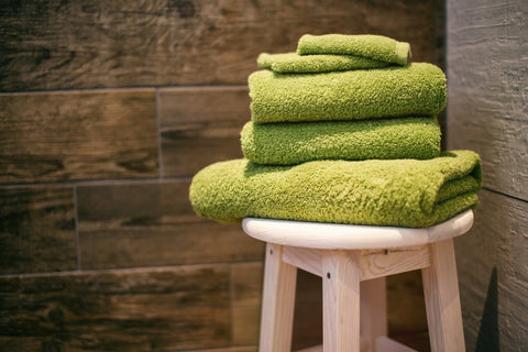 Green towels placed on a bench inside a sauna