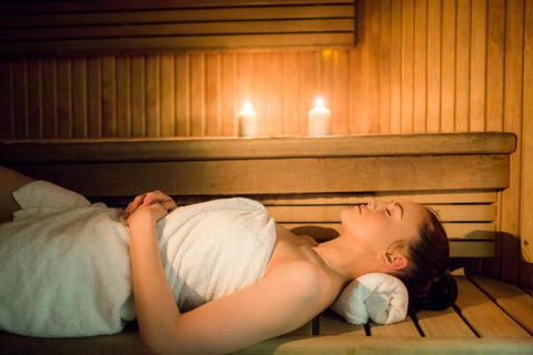 A woman enjoying muscle pain relief in the sauna.