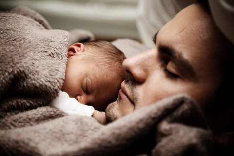 A young man sleeping while holding a baby.