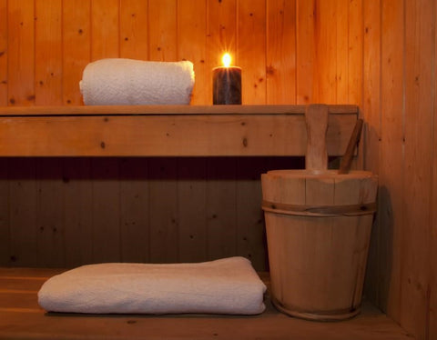 : Inside a wooden sauna, towel, candle and bucket