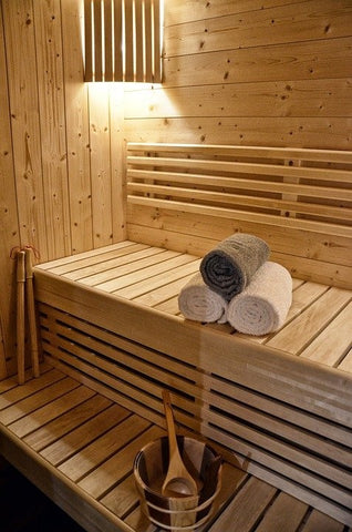 A wooden infrared sauna with towels and dim lighting