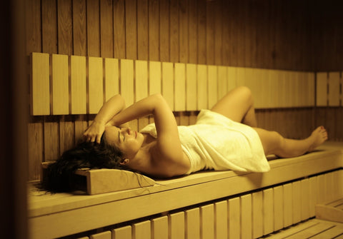 A woman wrapped in a towel relaxing in a sauna