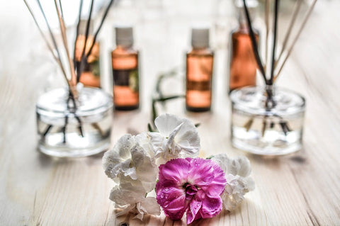 aromatherapy jars and white and purple flowers on a brown wooden surface