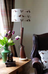 Gun table lamp with gamebird shade.