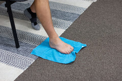 Man sitting in a chair using his foot to scrunch the blue towel