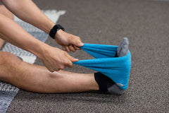 Man sits on the ground and uses the blue towel to stretch the foot.