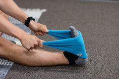 Man uses blue towel to stretch his foot