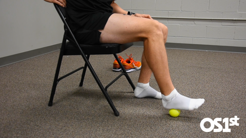 A man sitting in a chair rolling his foot on a tennis ball for Plantar Fasciitis