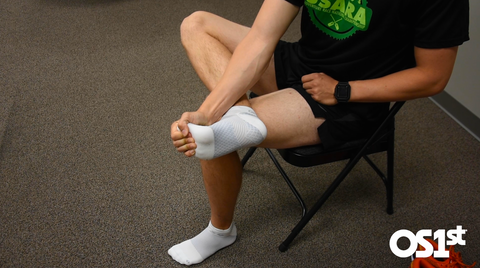 A man sitting in a chair with his leg crossed and using his hand to pull his toes towards his shin