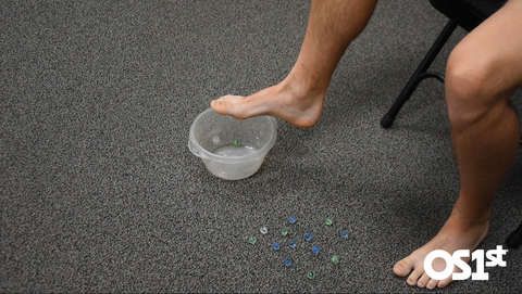 Feet that are being used to pick marbles up and place them in a bowl.