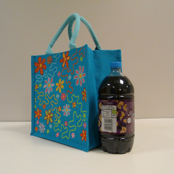 P1110514-Fair-Trade-Jute-Square-Shopping-Bag-Flowers-on-Blue-19704-side-view-with-bottle-of-juice