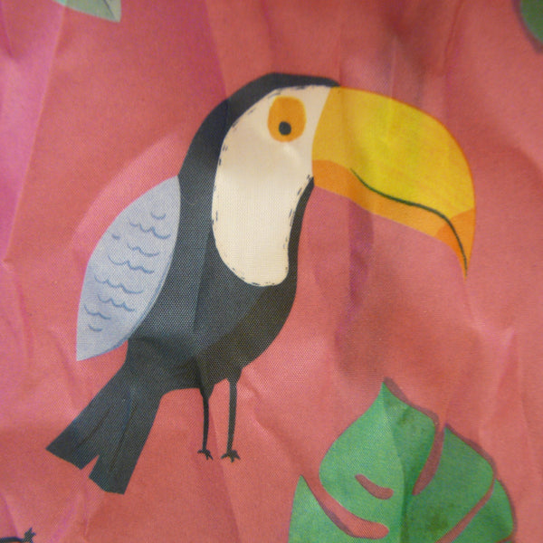 Detail of black and white Toucan with yellow/orange beak and pale blue wings. Also large leaf