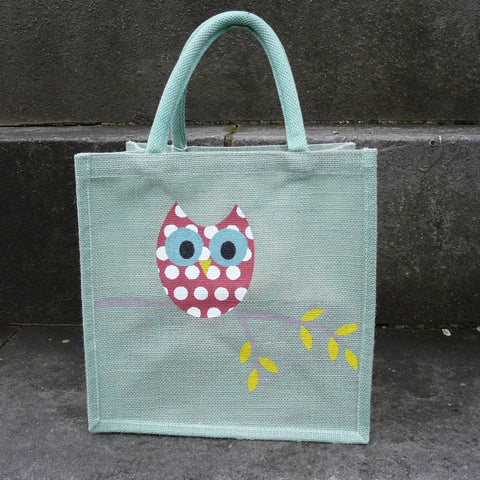 Pale green square jute bag with padded handles decorated with Red Owl with white spots on branch with yellow leaves
