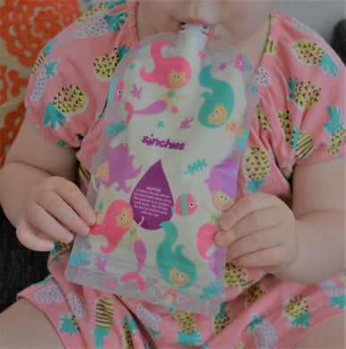 Toddler sucking yoghurt from a 200ml Sinchies reusable food pouch that has a mermaid design on it,