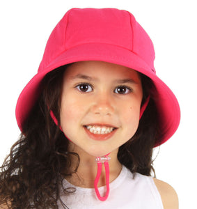 A girl wearing a bright pink bucket hat made by bedhead hats
