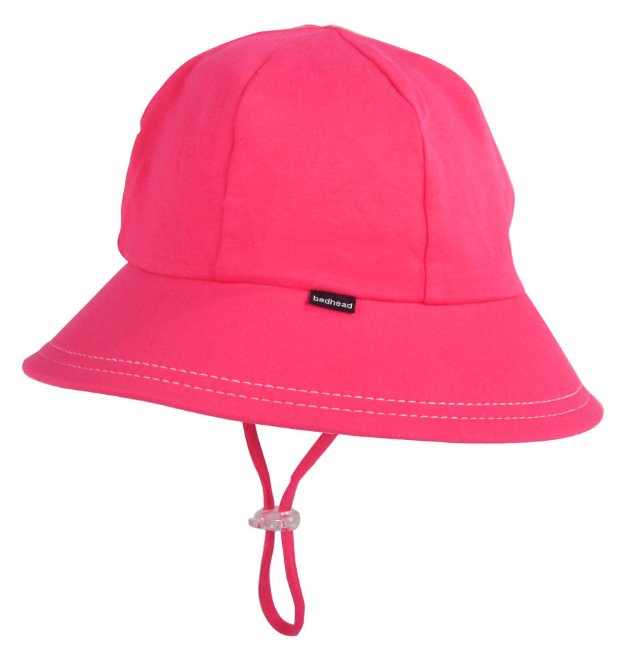 A side view of the bedhead girls ponytail bucket hat in bright pink