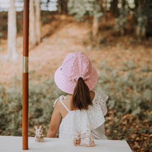 a girl wearing a bedhead ponytail bucket hat in daisy which has light pink and white daisies on a pink background and an adjustable chin strap. This picture shows the back view on her ponytail that can go through the ponytail keyhole in the back of the hat
