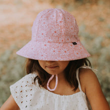 Load image into Gallery viewer, a girl wearing a bedhead ponytail bucket hat in daisy which has light pink and white daisies on a pink background and an adjustable chin strap. She is looking down