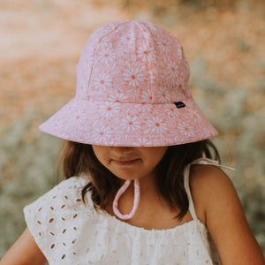 a girl wearing a bedhead ponytail bucket hat in daisy which has light pink and white daisies on a pink background and an adjustable chin strap. She is looking down