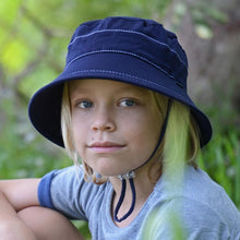 Load image into Gallery viewer, boy wearing a bedhead kids bucket hat in a navy blue colour
