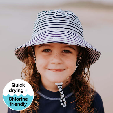 a kid at the beach wearing a bedhead beach bucket hat in striped with dark blue stripes on a white background