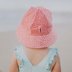 a girl on the beach wearing a bedhead beach bucket hat in a spot print with wonky pale pink spots on a darker pink background. this picture shows the back of the hat with the ponytail slit