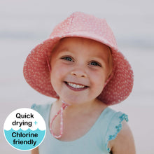 Load image into Gallery viewer, a girl on the beach wearing a bedhead beach bucket hat in a spot print with wonky pale pink spots on a darker pink background
