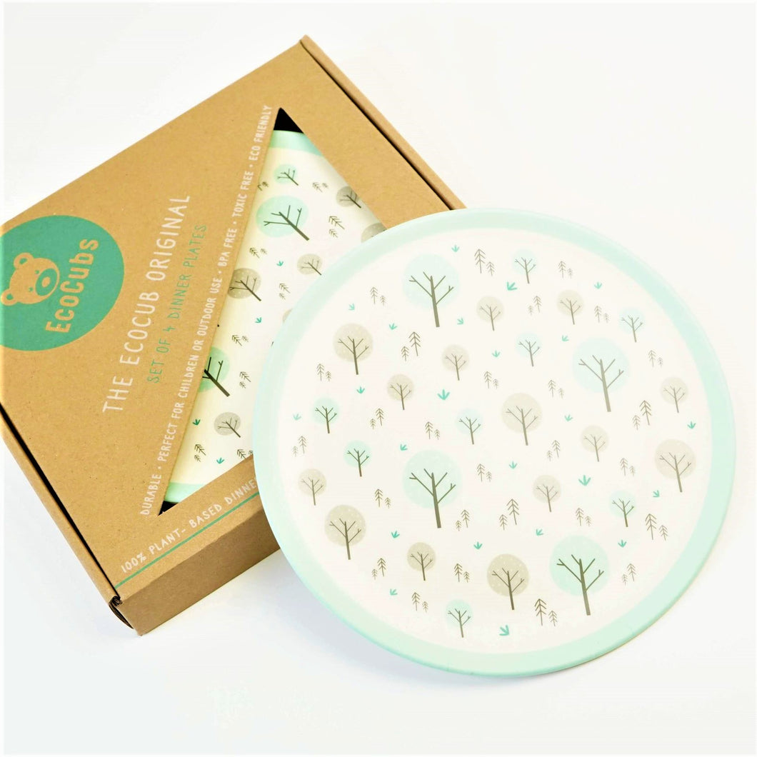 A set of four Ecocubs plant based dinner plates. They are 25cm in diameter and have a white background with an aqua blue rim. They are made of bamboo and come in cardboard packaging.