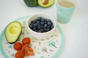 Ecocubs plant based dinnerware including a small bamboo bowl filled with blueberries, sitting on a large bamboo plate that also has half an avocado and tomatoes and next to a bamboo cup filled with water.