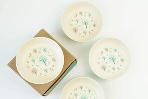 A set of four large bamboo bowls made by EcoCubs Australia. They are aqua blue on the underside and white on the upper side with a design in the centre of blue and grey trees. These are plant based dinnerware. This photo shows them front the top view and one bowl is sitting on top of the cardboard packaging.