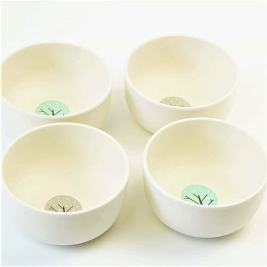 EcoCubs plant based dinnerware bamboo bowls in a small snack size. This photo is a set of four white bowls, two with a blue circle and a tree in the middle and two with a grey circle and a tree.