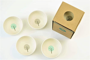 EcoCubs plant based dinnerware bamboo bowls in a small snack size. This photo is a set of four white bowls, two with a blue circle and a tree in the middle and two with a grey circle and a tree. This photo also shoes a set of 4 bowls in their cardboard packaging