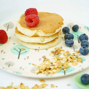 A set of four Ecocubs bamboo small plates. They are 19.5cm in diameter. They have a white background and aqua blue and grey tree design on them. They are 100% plant based. This photo shows one plate with pancakes, raspberries and blueberries.