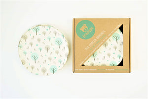 A set of four Ecocubs bamboo small plates. They are 19.5cm in diameter. They have a white background and aqua blue and grey tree design on them. They are 100% plant based. This photo also shows them in their cardboard packaging.