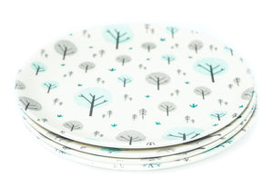 A set of four Ecocubs bamboo small plates. They are 19.5cm in diameter. They have a white background and aqua blue and grey tree design on them. They are 100% plant based.