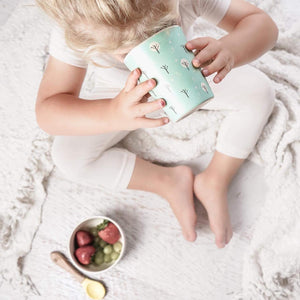 A set of four kid size Ecocubs tumbler cups. These cups are made from bamboo and are 100% plant based, Two of the cups have an aqua blue background and two cups are white. This photo shows a young girl drinking from the cup