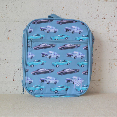 A MontiiCo insulated lunch bag in a cars design that has black, white and light blue cars on a blue background. This is the front view.