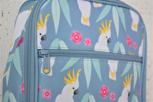 A MontiiCo insulated lunch bag in a cockatoo print which has sulpher crested cockatoos, gum leaves and pink gum blossoms on a slate, blue background. This is a close up view of the design and the zipper on the front pocket.