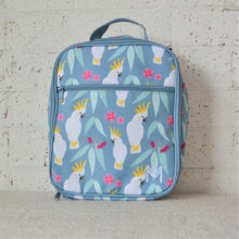 Load image into Gallery viewer, A MontiiCo insulated lunch bag in a cockatoo print which has sulpher crested cockatoos, gum leaves and pink gum blossoms on a slate, blue background. This is the front view.
