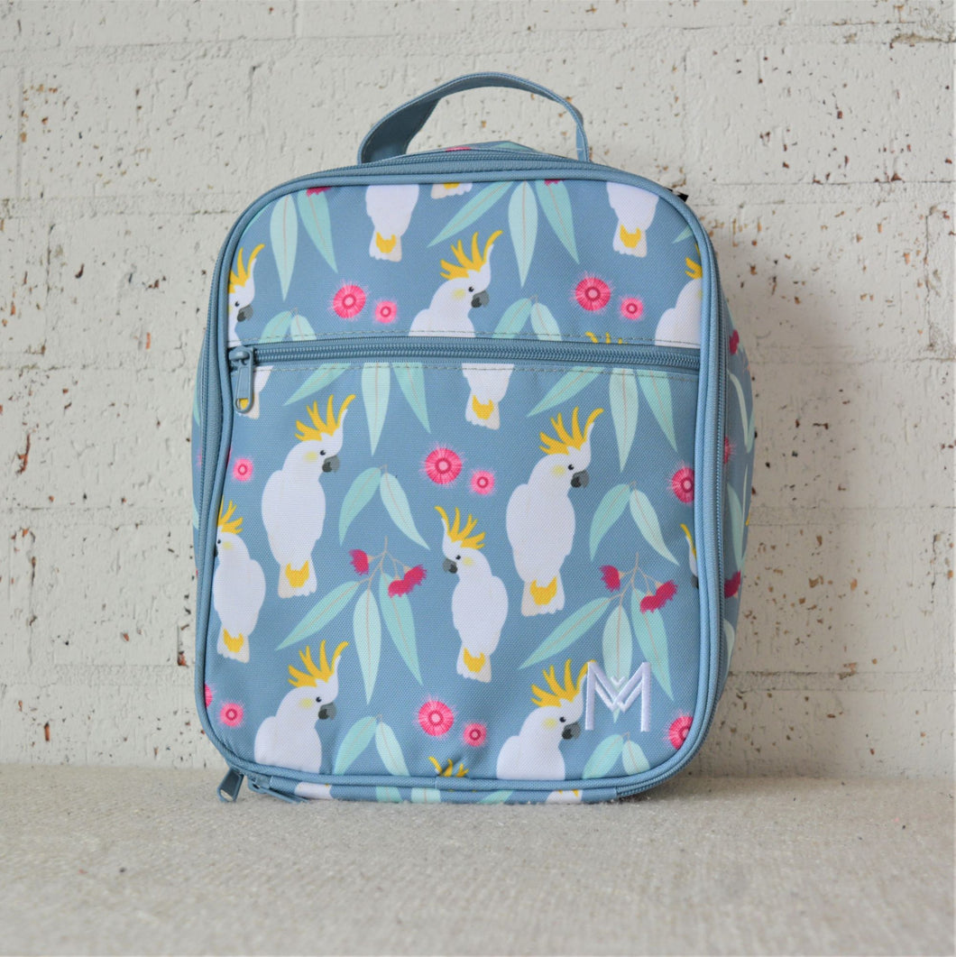 A MontiiCo insulated lunch bag in a cockatoo print which has sulpher crested cockatoos, gum leaves and pink gum blossoms on a slate, blue background. This is the front view.