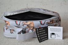 Load image into Gallery viewer, A MontiiCo insulated lunch bag in the 2020 dinosaur design which has brown triceratops and green and red velociraptor dinosaurs o a grey slate background. This picture shows the back pocket open which is a separate compartment for the included ice pack.